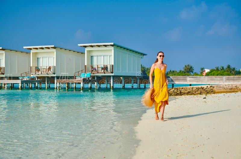 Mulher no vestido que corre na praia tropical foto de stock