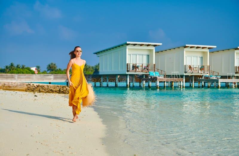 Mulher no vestido que corre na praia tropical imagens de stock royalty free