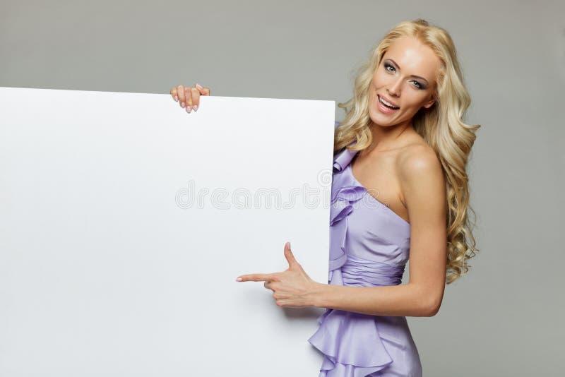 Mulher no vestido roxo que guardara o whiteboard vazio imagens de stock