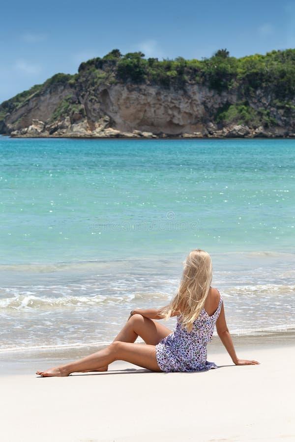 Mulher no vestido roxo que levanta na praia só imagem de stock