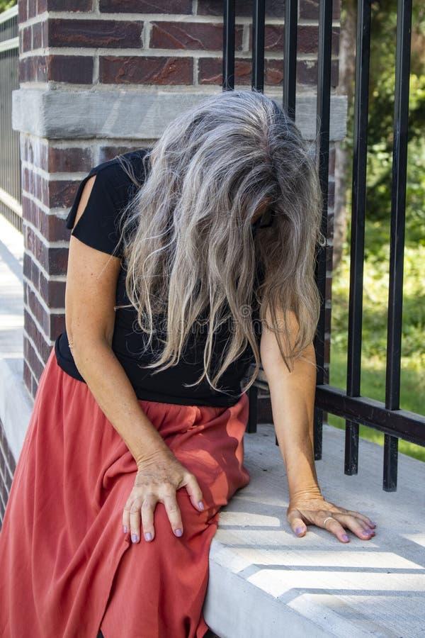 A mulher no vestido senta-se pela cerca com sua cabeça curvada e cara coberta com o cabelo cinzento longo doente ou triste ou na  foto de stock royalty free