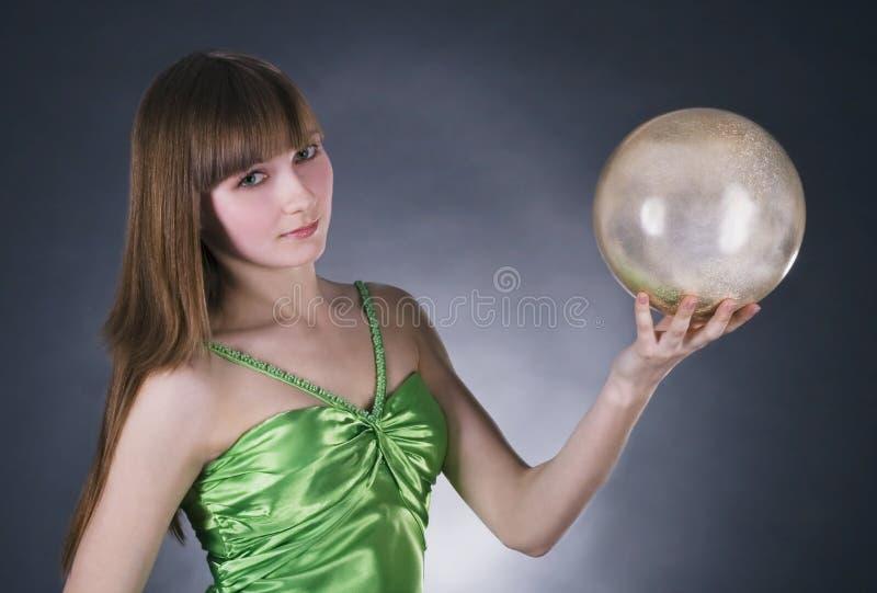 mulher no vestido verde com esfera do ouro imagens de stock royalty free