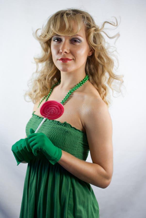 Mulher no vestido verde que guardara o pirulito fotos de stock