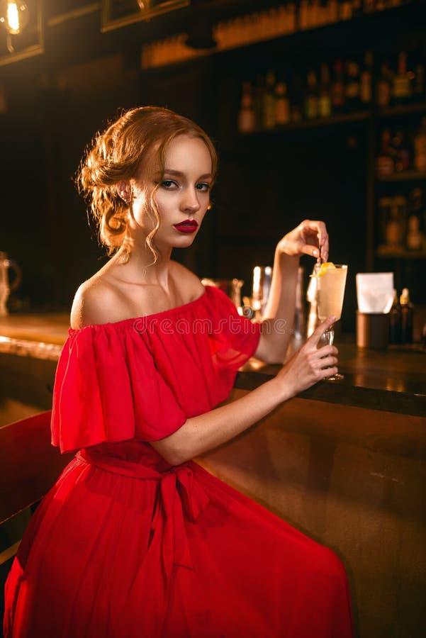 A mulher no vestido vermelho bebe o cocktail no contador da barra foto de stock