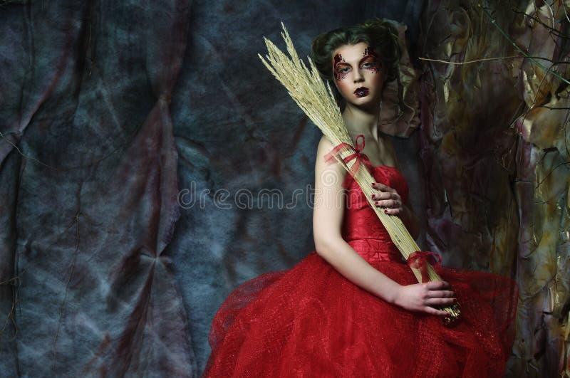 Mulher no vestido vermelho O penteado fantástico e compõe fotografia de stock