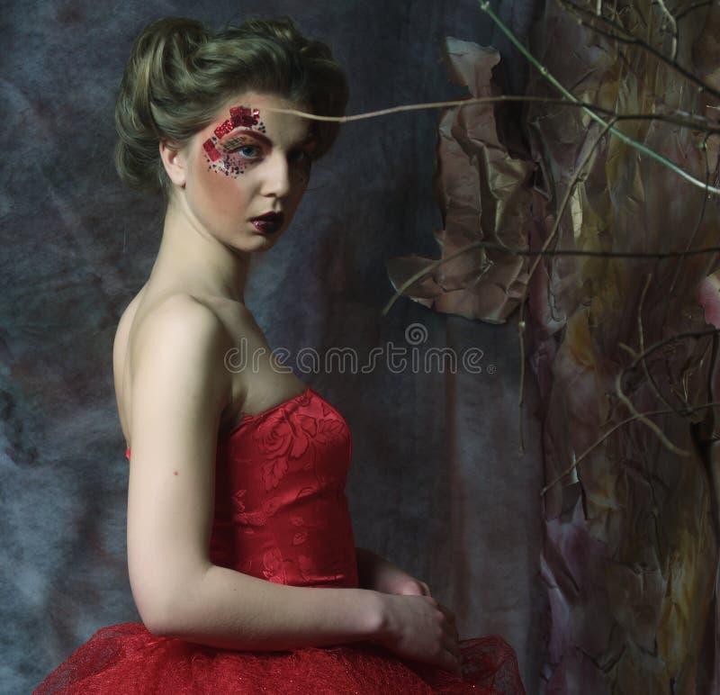 Mulher no vestido vermelho O penteado fantástico e compõe fotografia de stock royalty free