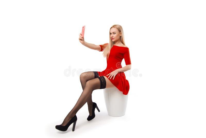 Mulher no vestido vermelho - selfie móvel no branco imagens de stock royalty free