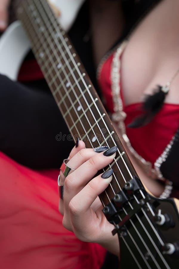 Mulher no vestido vermelho 'sexy' que guarda a guitarra elétrica com foco em sua mão em cordas do pescoço da guitarra imagens de stock
