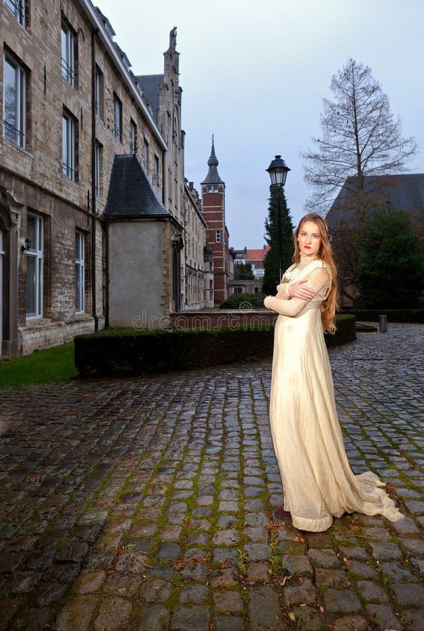 Mulher no vestido vitoriano em um quadrado de cidade velho na noite no perfil imagens de stock