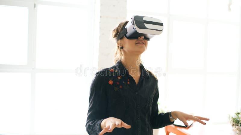 Mulher nos auriculares de VR que olham acima e que tentam tocar em casa em objetos na realidade virtual dentro imagens de stock royalty free