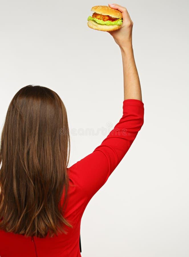 Mulher nos dres vermelhos que estão para trás e que mostram o hamburguer imagens de stock royalty free