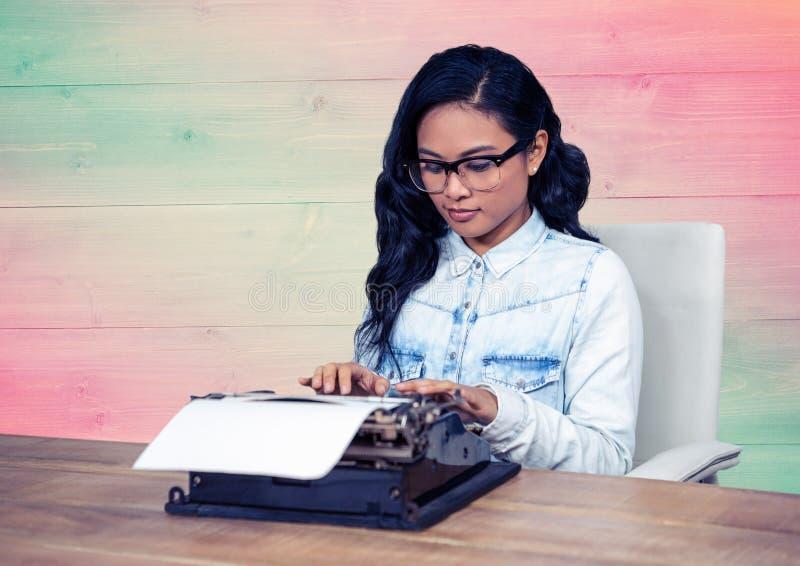 Mulher nos espetáculos usando a máquina de escrever no escritório fotografia de stock