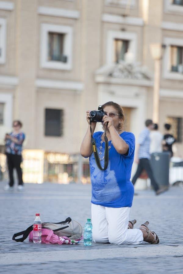 Mulher nos joelhos que tomam uma imagem fotos de stock royalty free