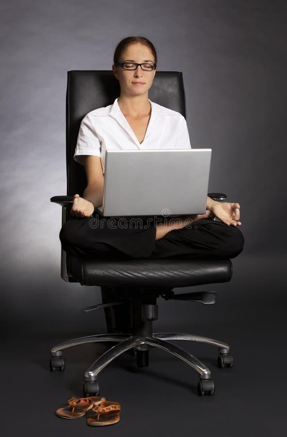 A mulher nos lótus levanta na cadeira com portátil. imagens de stock royalty free