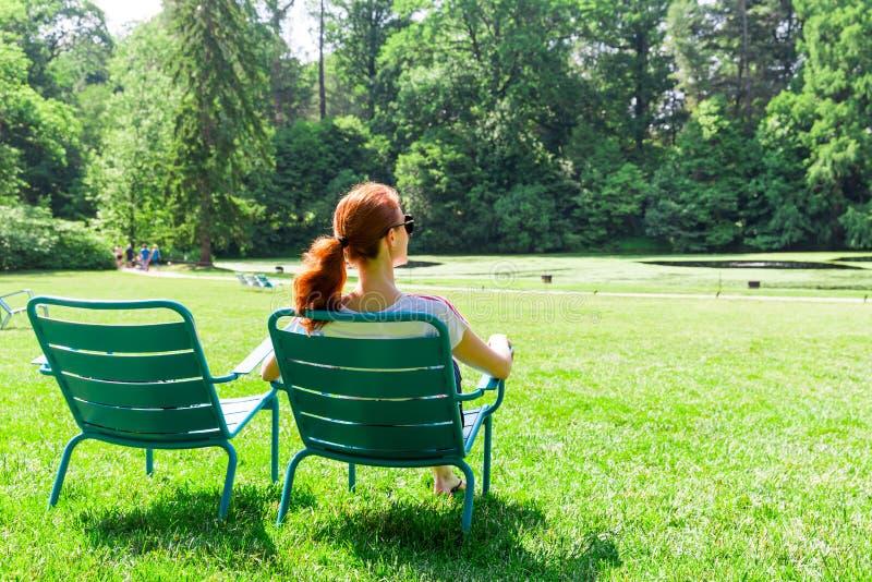 A mulher nos monóculos relaxa no Greenfield imagem de stock royalty free