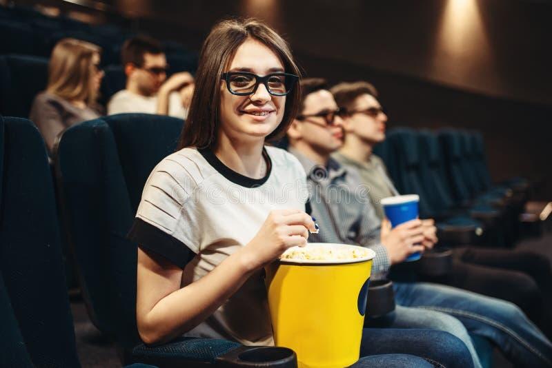 Mulher nos vidros 3d que sentam-se no assento no cinema fotos de stock royalty free