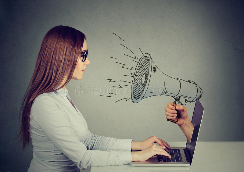 Mulher nos vidros que sentam-se na tabela usando o trabalho em um computador com o megafone que pica para fora de uma tela do por imagem de stock