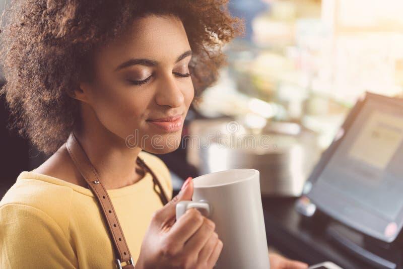 A mulher nova agradável do mulato está relaxando com cappuccino no trabalho imagem de stock royalty free