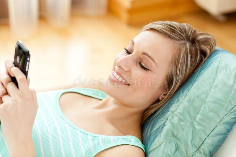 Mulher nova alegre que emite um texto que encontra-se em um sofá foto de stock royalty free