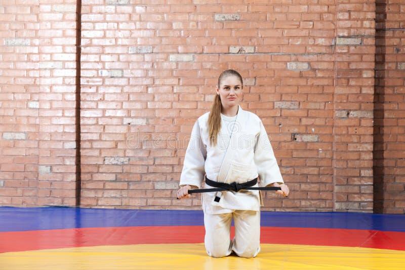 Mulher nova atlética bonita do karaté no quimono branco no fightin imagens de stock