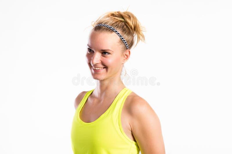 Mulher nova atrativa da aptidão na camiseta de alças amarela Tiro do estúdio imagem de stock