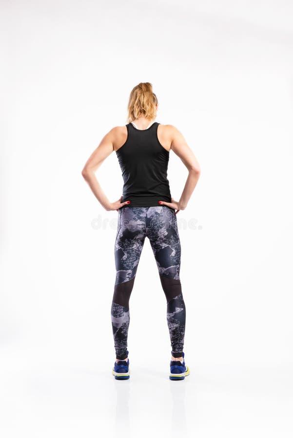Mulher nova atrativa da aptidão no equipamento preto Tiro do estúdio imagem de stock royalty free