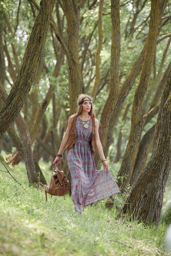 Mulher nova atrativa da hippie que anda entre árvores na floresta foto de stock