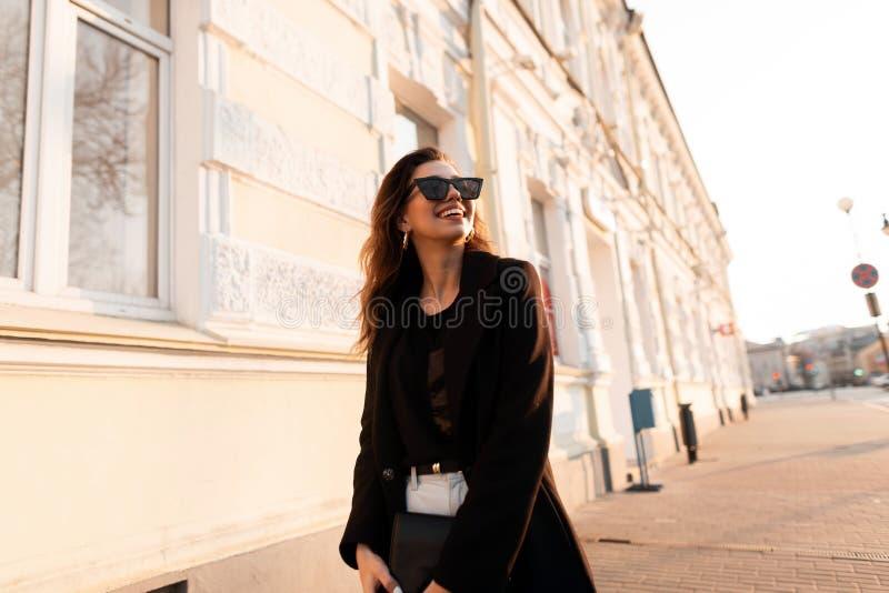 Mulher nova atrativa do moderno com um sorriso positivo em um revestimento elegante nos óculos de sol em um t-shirt nas calças de fotografia de stock royalty free