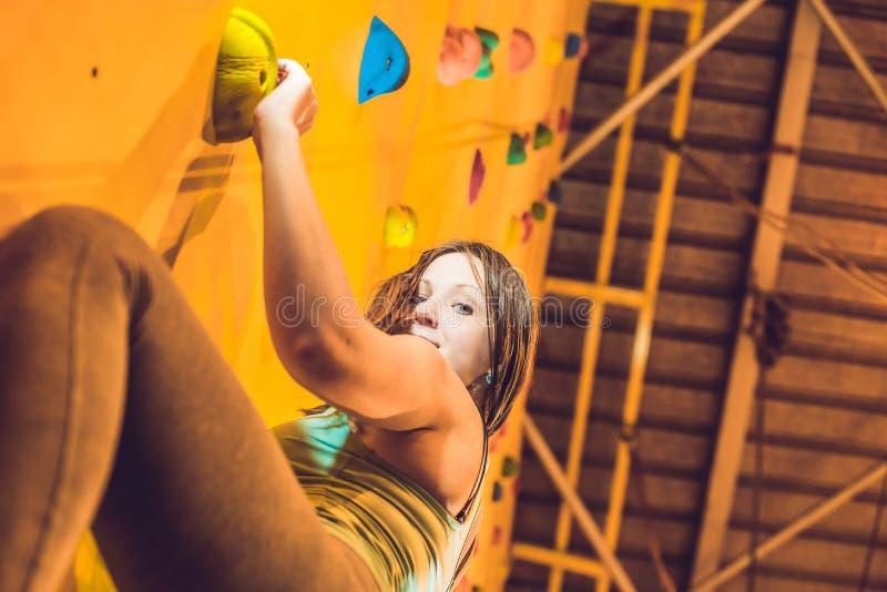 Mulher nova atrativa do montanhista do esporte profissional que tem o treinamento no gym na parede artificial fotos de stock