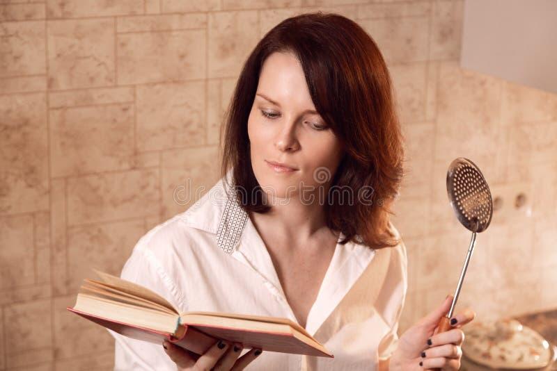 Mulher nova atrativa do ruivo que lê um livro ao cozinhar na cozinha imagem de stock