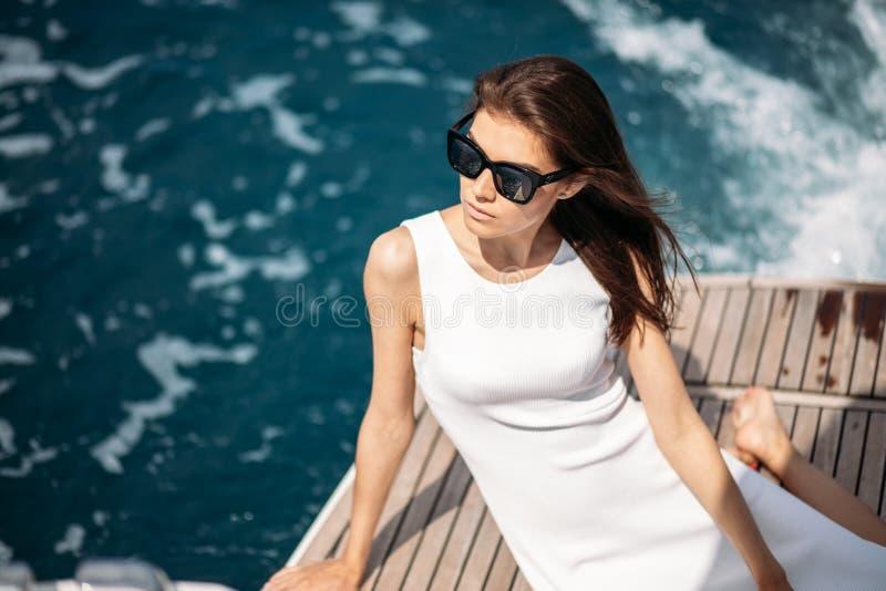 Mulher nova, atrativa e rica que tem o fotossesion em um barco luxuoso no mar fotografia de stock