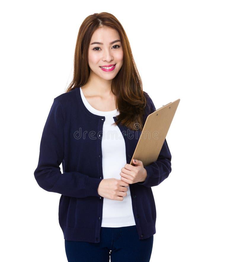 A mulher nova atrativa escreve com uma prancheta imagens de stock