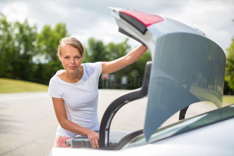 Mulher nova, atrativa, feliz que toma uma mala de viagem de seu carro fotos de stock royalty free