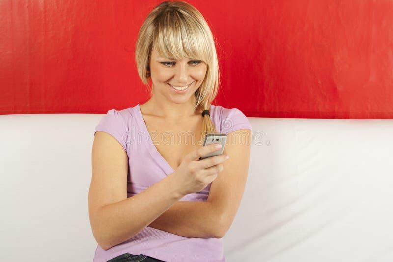 Mulher nova atrativa no sofá com o telefone foto de stock royalty free