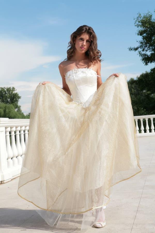Mulher nova atrativa no vestido branco-dourado imagem de stock royalty free