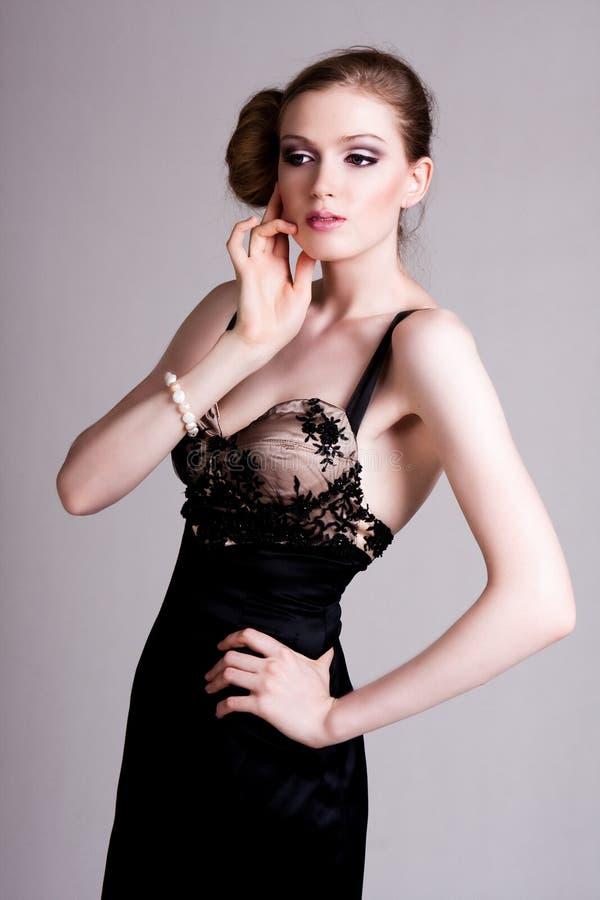Mulher nova atrativa que desgasta um vestido preto fotografia de stock royalty free