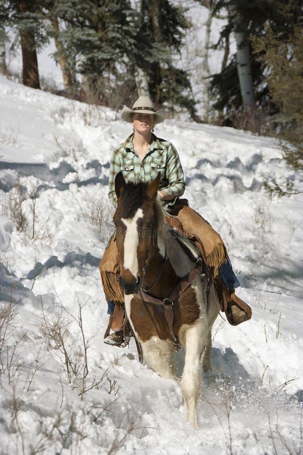 Mulher nova atrativa que monta um cavalo a neve foto de stock