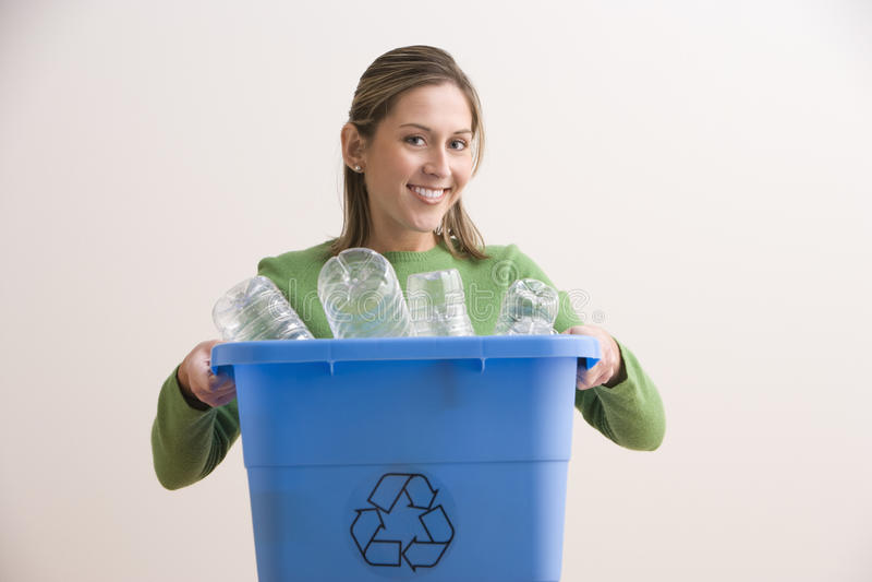 A mulher nova atrativa que prende um azul recicl o escaninho foto de stock royalty free