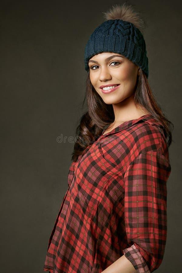 Mulher nova, atrativa, sorrindo em uma camisa de manta vermelha fotografia de stock