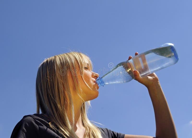 A mulher nova bebe a água foto de stock royalty free