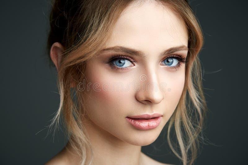 Mulher nova bonita com as flores frescas em seu cabelo que olha para baixo Conceito da mola imagens de stock royalty free