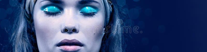 Mulher nova bonita com composição azul Isolado no azul foto de stock royalty free