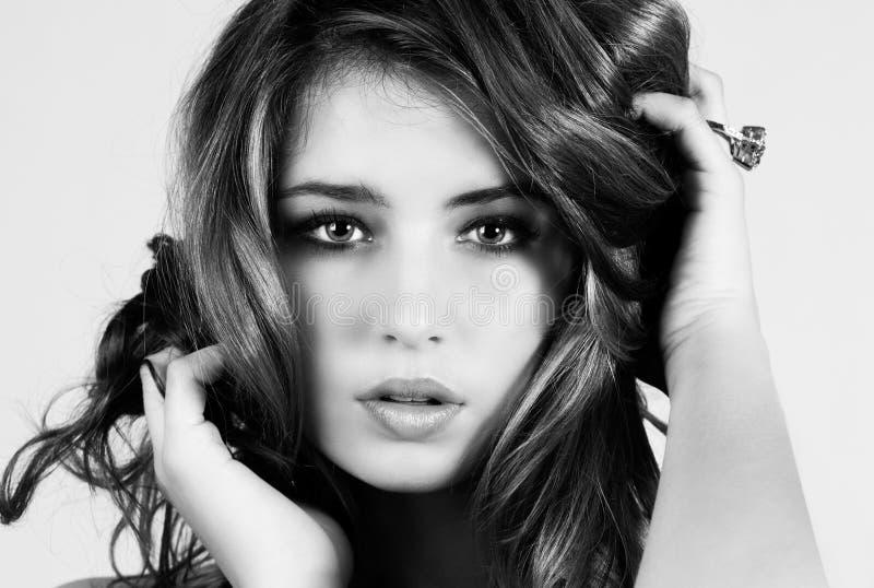 Mulher nova bonita com mãos em seu cabelo foto de stock
