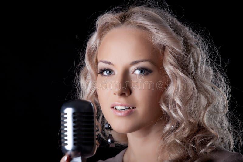 Mulher nova bonita com microfone foto de stock royalty free