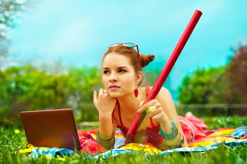 Mulher nova bonita com portátil e lápis na GR foto de stock