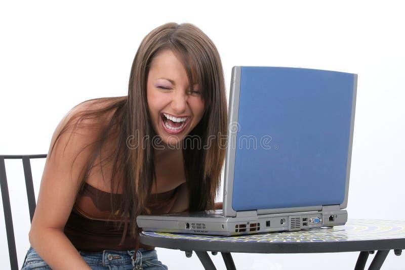 Mulher nova bonita com riso do computador portátil