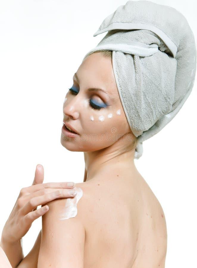 A mulher nova bonita com um creme cosmético foto de stock royalty free