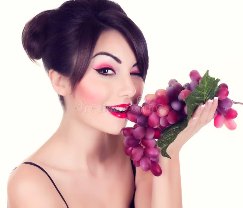 Mulher nova bonita com uva vermelha fotos de stock royalty free