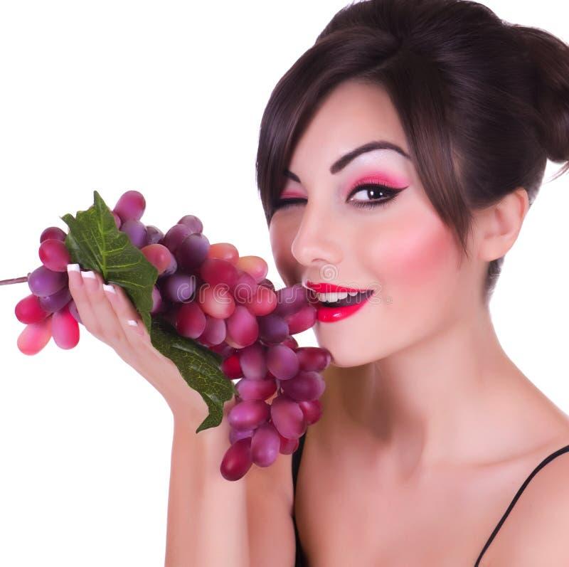 Mulher nova bonita com uva vermelha fotografia de stock royalty free