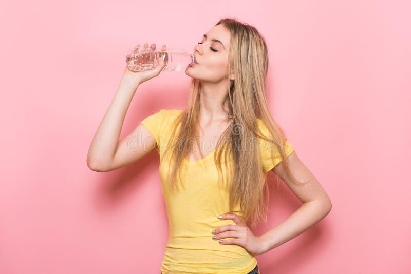 Mulher nova bonita da aptidão com forma perfeita do corpo que bebe a água fresca da garrafa plástica que está perto da parede cor fotografia de stock